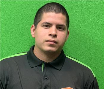 Male in SERVPRO crew shirt, black with green, on green back drop